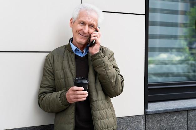 Smiley oudere man in de stad die op smartphone praat terwijl hij koffie drinkt
