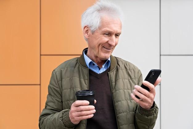 Smiley oudere man in de stad die smartphone gebruikt terwijl hij koffie drinkt