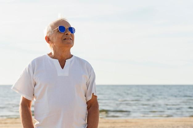 Smiley oudere man met zonnebril genieten van zijn tijd op het strand