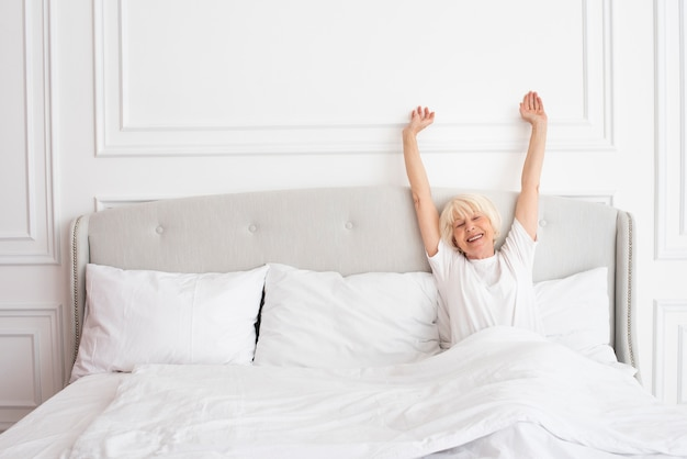 Smiley oudere vrouw die in de slaapkamer legt
