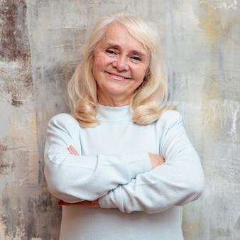 Smiley oudere vrouw die zich naast bevroren venster bevindt