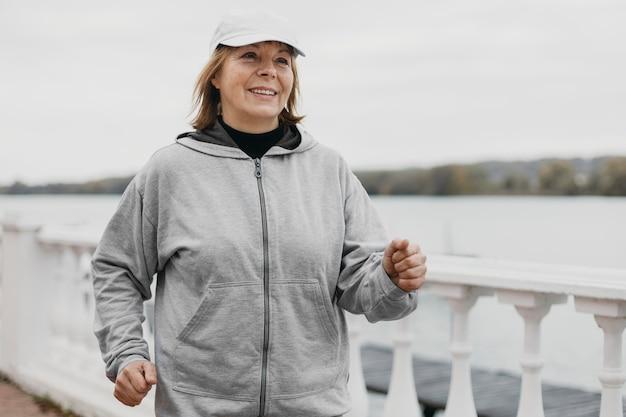 Smiley oudere vrouw joggen buitenshuis