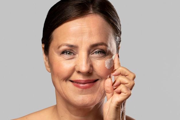 Smiley oudere vrouw met behulp van vochtinbrengende crème op haar gezicht