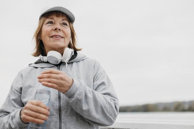 Smiley oudere vrouw met fles water en koptelefoon buitenshuis