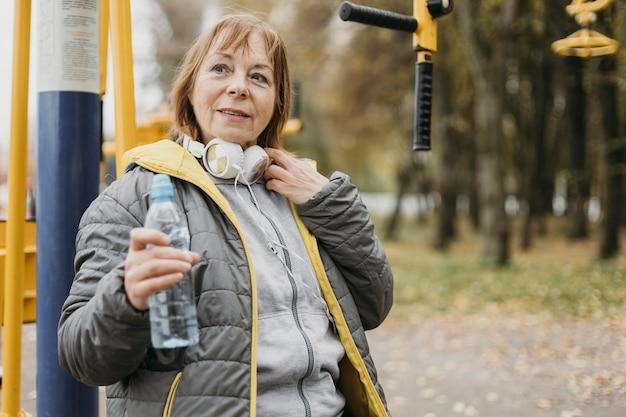 Smiley oudere vrouw met koptelefoon drinkwater na het trainen buitenshuis