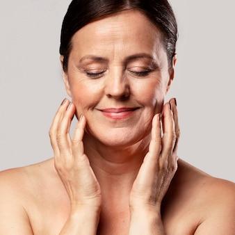 Smiley oudere vrouw met make-up bij het poseren met de handen op het gezicht