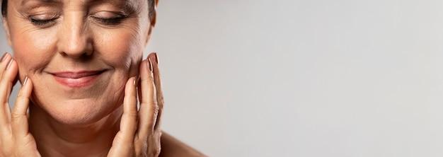 Smiley oudere vrouw met make-up bij het stellen met handen op gezicht en kopieer de ruimte