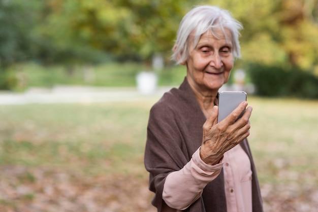 Smiley oudere vrouw met smartphone buitenshuis met kopie ruimte