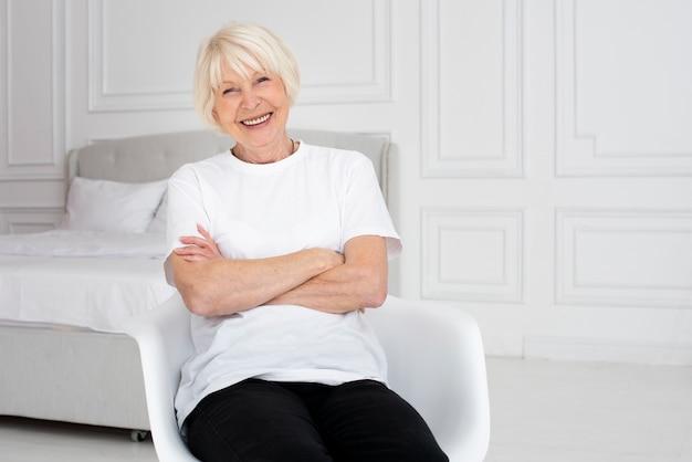 Smiley oudere vrouw zittend op stoel