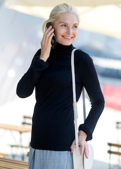 Smiley oudere zakenvrouw buitenshuis op een telefoontje