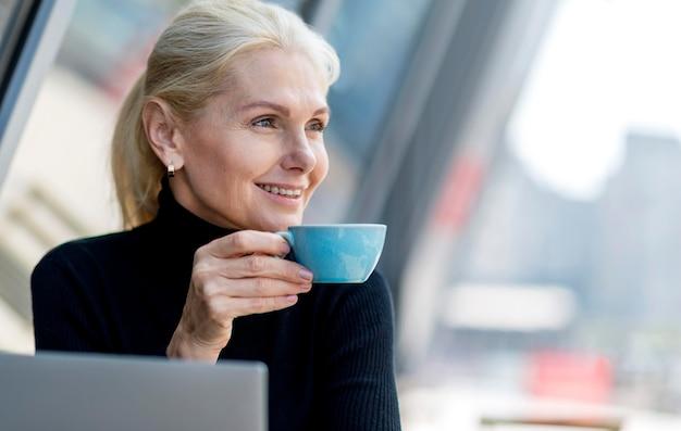Smiley oudere zakenvrouw met koffie buitenshuis tijdens het werken