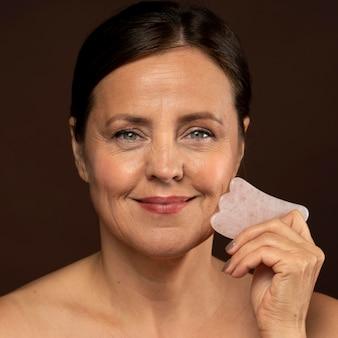 Smiley rijpe vrouw met behulp van rozenkwarts gezicht beeldhouwer