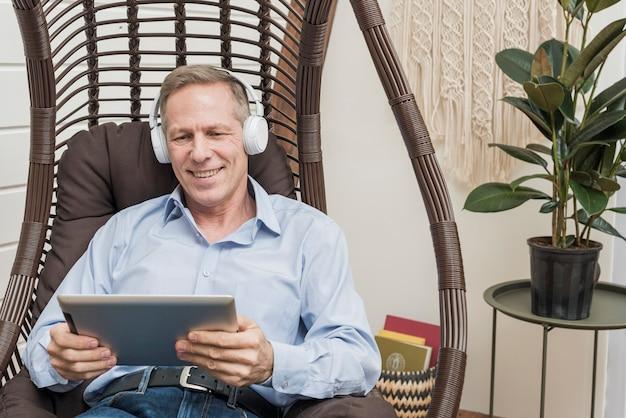 Smiley senior man luisteren naar muziek hoewel koptelefoon