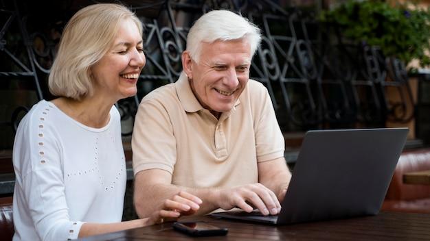 Smiley senior paar buiten zitten en kijken en laptop