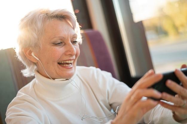 Smiley senior vrouw luisteren muziek