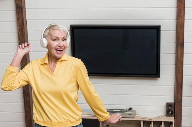 Smiley senior vrouw luisteren naar muziek via draadloze koptelefoon