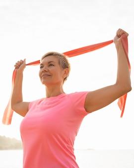 Smiley senior vrouw met elastisch touw op het strand
