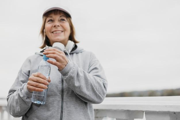 Smiley senior vrouw met fles water en koptelefoon buitenshuis