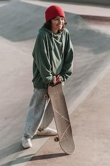 Smiley tiener met skateboard buiten in het skatepark
