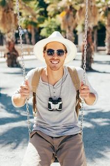 Smiley toerist poseren op de swing