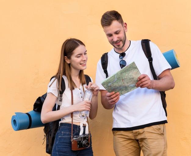 Smiley toeristenpaar met rugzakken en kaart