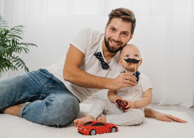 Smiley vader poseren met baby tijdens het spelen