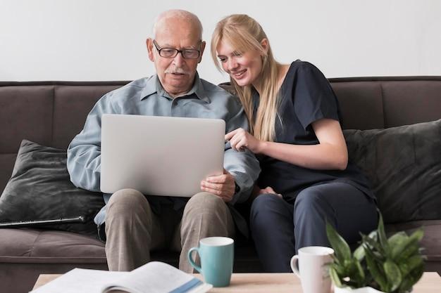 Smiley verpleegster die oude man laptop toont