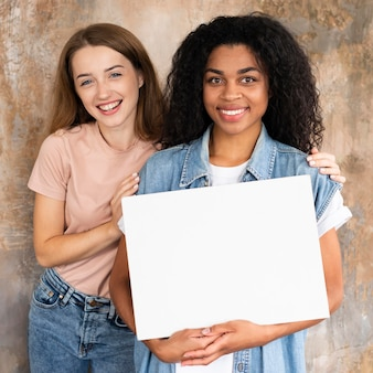 Smiley vriendinnen die samen poseren terwijl ze leeg bordje vasthoudt