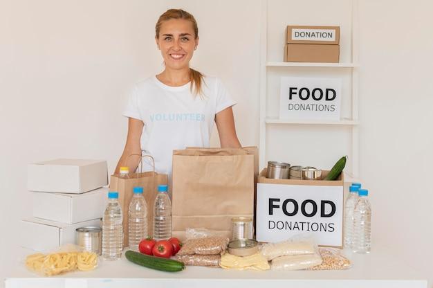Smiley-vrijwilliger poseren met zakken met voedseldonaties