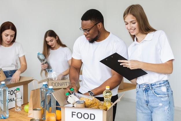 Smiley-vrijwilligers die doos met voedsel voorbereiden voor donatie