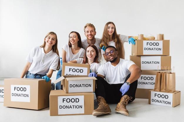 Smiley-vrijwilligers poseren samen met donatieboxen met eten
