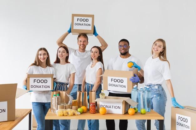 Smiley-vrijwilligers poseren samen met donatieboxen