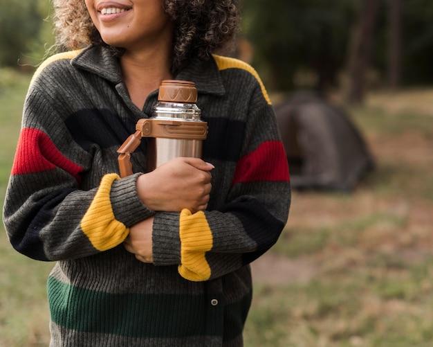 Smiley vrouw buitenshuis camping bedrijf thermos