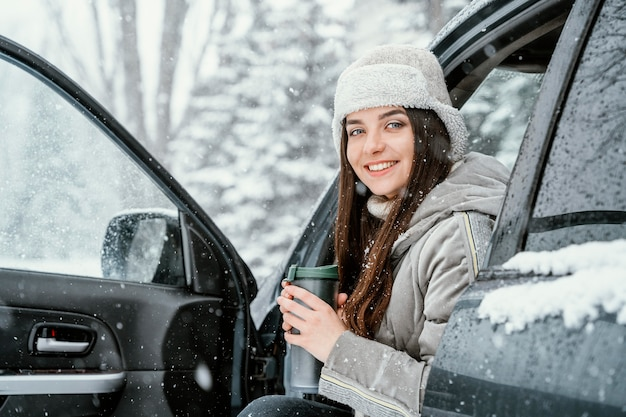 Smiley-vrouw drinkt een warm drankje en geniet van de sneeuw tijdens een roadtrip