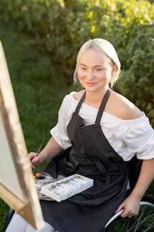 Smiley vrouw in rolstoel buiten in natuur schilderij