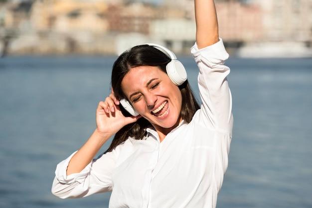 Smiley vrouw luisteren naar muziek op een koptelefoon op het strand