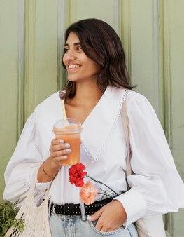 Smiley vrouw met boodschappentassen en bloemen met sap buitenshuis