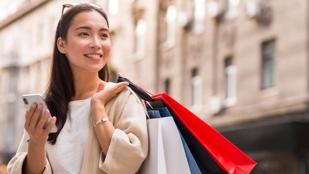 Smiley vrouw met boodschappentassen en smartphone buitenshuis