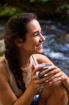 Smiley vrouw met koffie tijdens het verkennen van de natuur