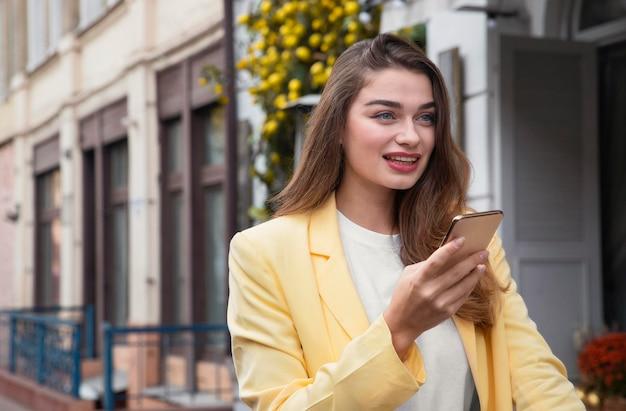 Smiley vrouw met smartphone terwijl je op een fiets zit
