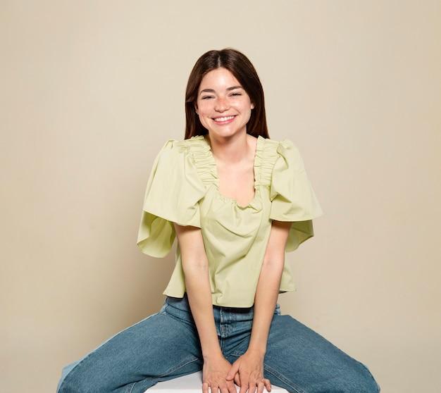Smiley vrouw poseren en zitten