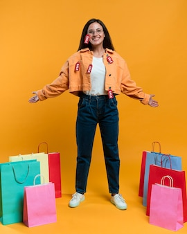 Smiley vrouw poseren met boodschappentassen en verkoop tags