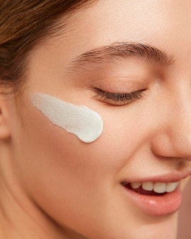 Smiley vrouw poseren met gezichtscrème