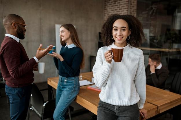 Smiley vrouw poseren terwijl koffiemok tijdens een kantoorvergadering
