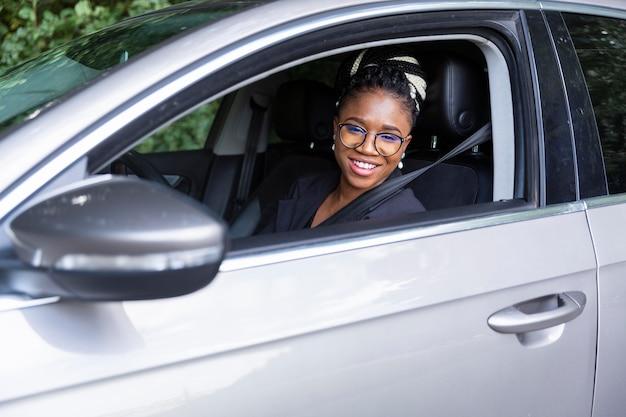 Smiley vrouw poseren vanaf de binnenkant van haar auto
