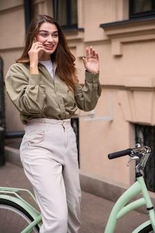 Smiley vrouw praten aan de telefoon tijdens het fietsen