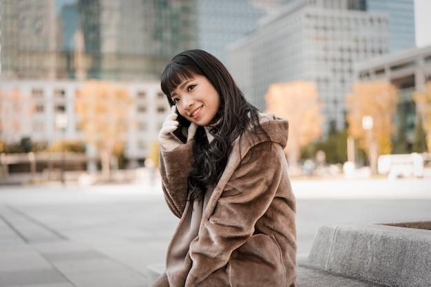 Smiley vrouw praten over de telefoon buitenshuis