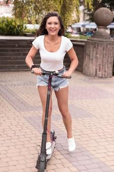 Smiley vrouw rijden scooter in de stad