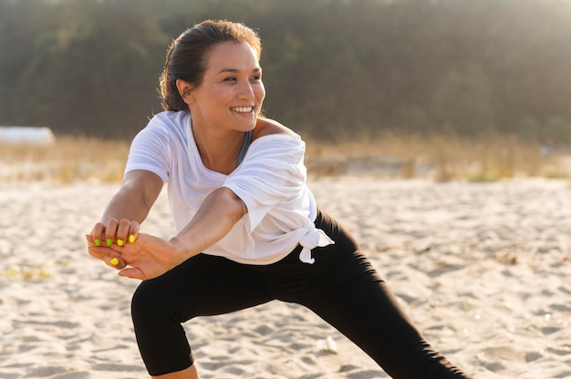 Smiley vrouw training op het strand