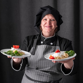 Smiley vrouwelijke chef-kok met gerechten in beide handen